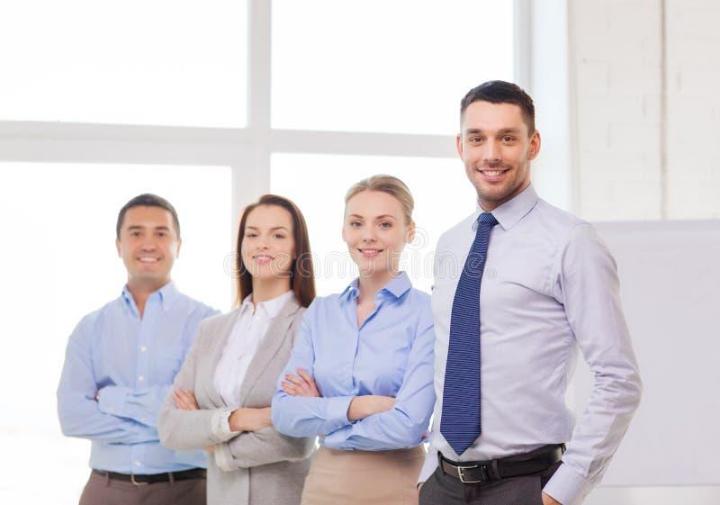 Homem de negócios de sorriso no escritório com parte traseira da equipe sobre imagens de stock