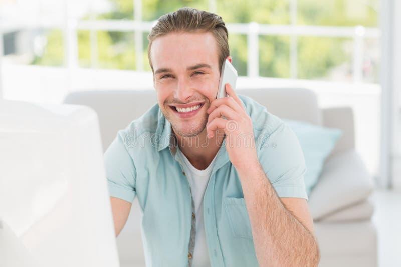 Homem de negócios de sorriso no telefone ao usar o computador imagens de stock royalty free