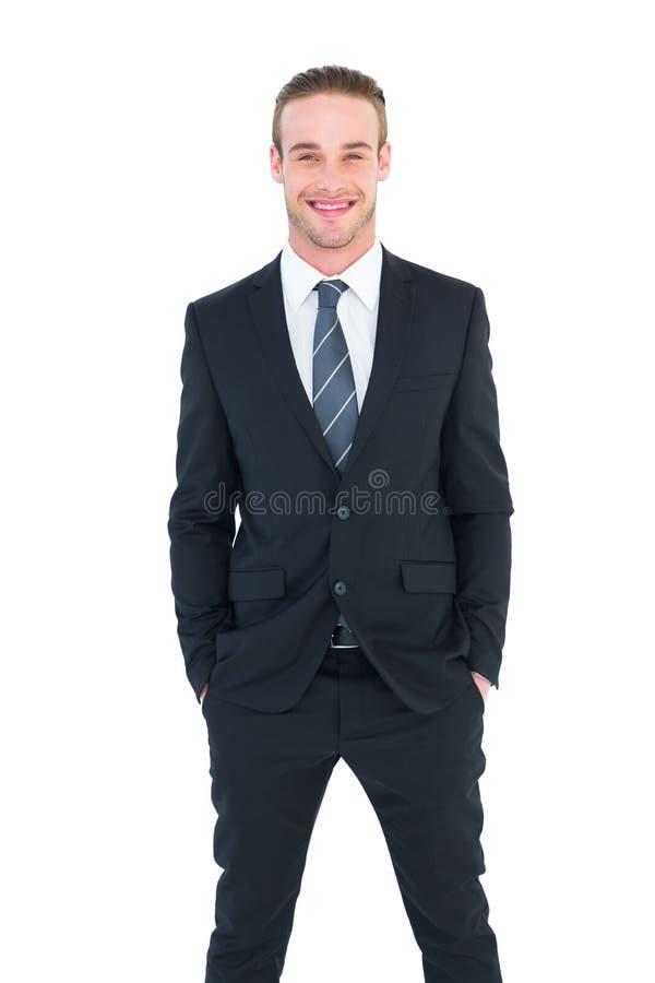 Homem de negócios de sorriso no terno com mãos no levantamento do bolso fotografia de stock