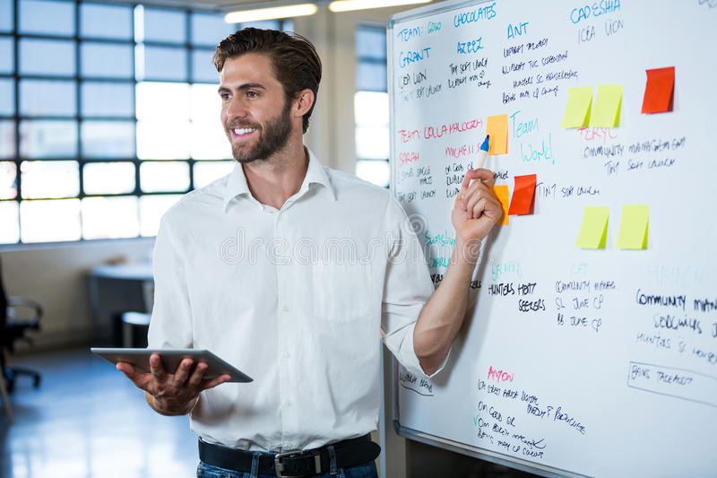 Homem de negócios de sorriso que aponta no whiteboard fotos de stock