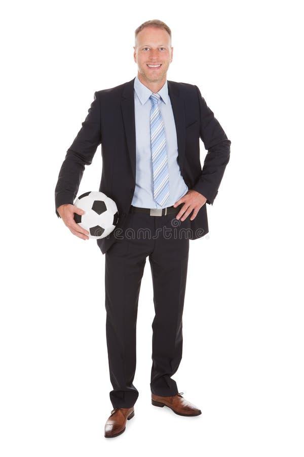 Homem de negócios de sorriso que guarda a bola de futebol imagens de stock