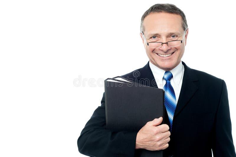 Homem de negócios de sorriso que guarda pastas de arquivos imagem de stock