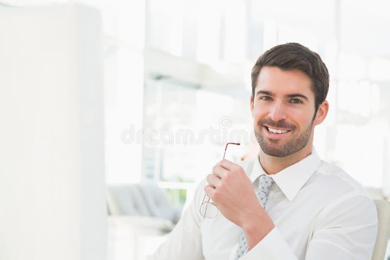 Homem de negócios de sorriso que guarda seus vidros foto de stock