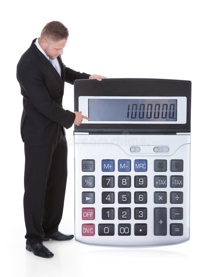 Homem de negócios de sorriso que indica uma calculadora imagem de stock royalty free