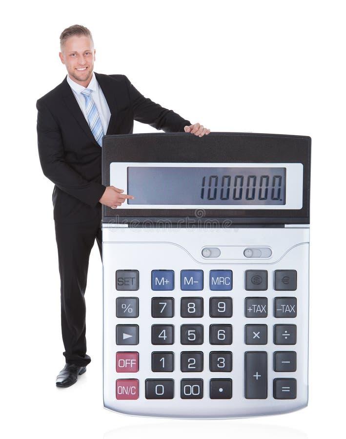 Homem de negócios de sorriso que indica uma calculadora fotos de stock