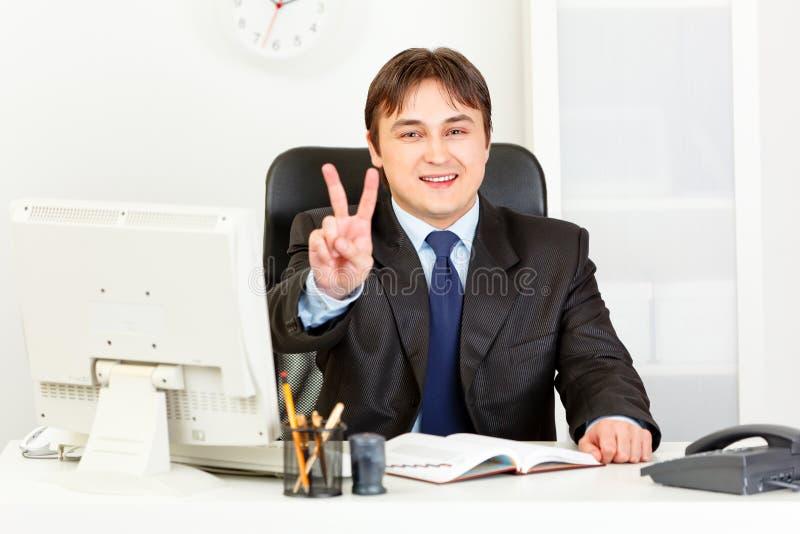 Homem de negócios de sorriso que mostra o gesto da vitória imagens de stock royalty free