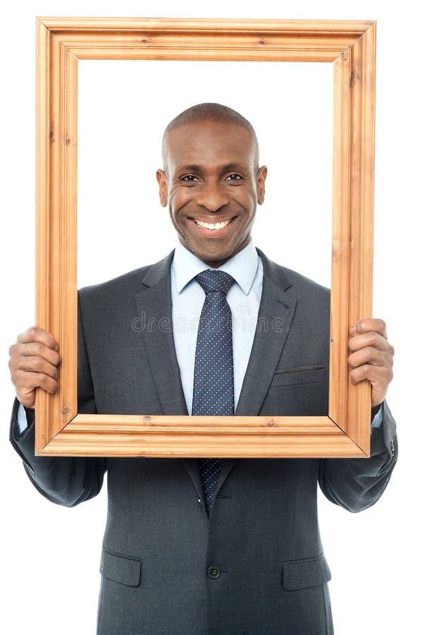 Homem de negócios de sorriso que olha através da moldura para retrato imagem de stock