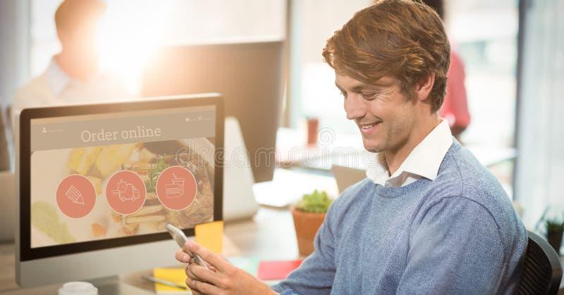 Homem de negócios de sorriso que usa o telefone celular na mesa do computador imagens de stock royalty free