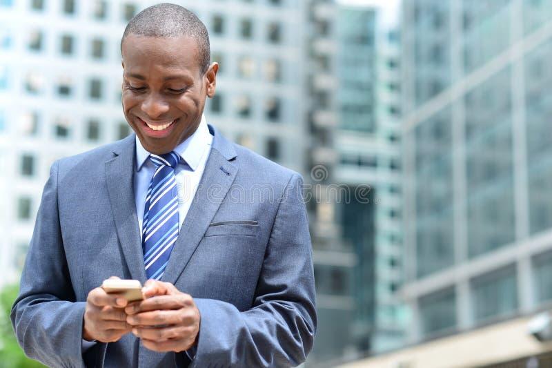 Homem de negócios de sorriso que usa seu smartphone fotos de stock royalty free