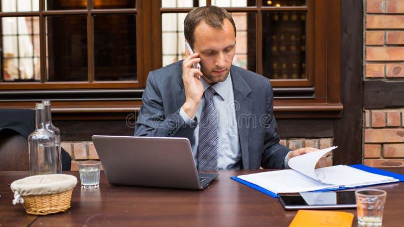 Homem de negócios de trabalho duro no restaurante com portátil e telemóvel. imagem de stock royalty free
