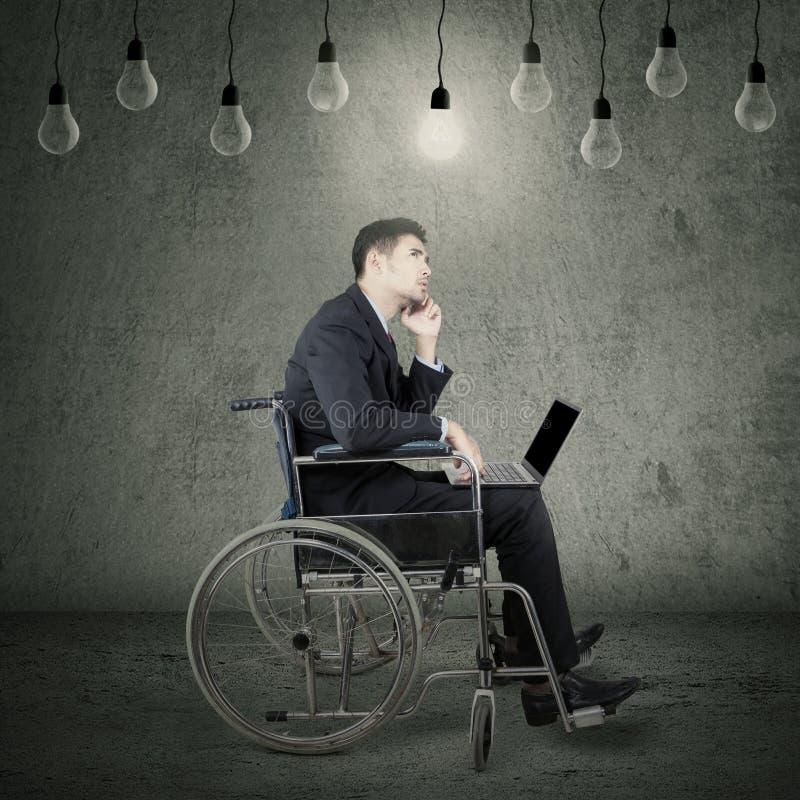 Homem de negócios deficiente pensativo na cadeira de rodas fotografia de stock royalty free