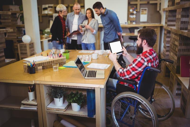 Homem de negócios deficiente que usa a tabuleta digital na mesa fotografia de stock