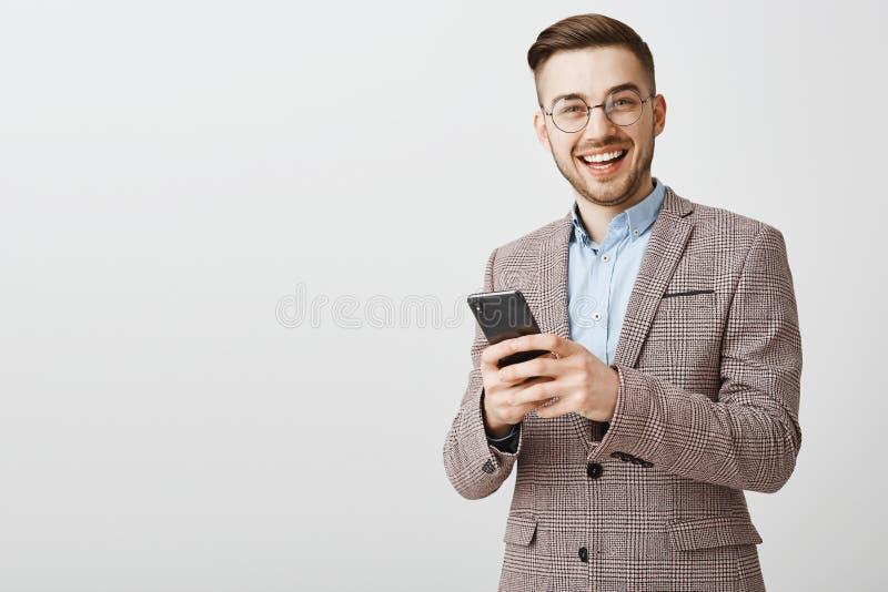 Homem de negócios deleitado bonito ambicioso nos vidros e no revestimento à moda que guardam o smartphone que olha na câmera aleg fotos de stock