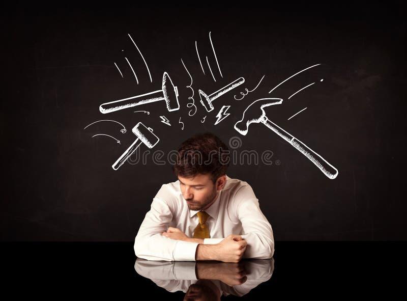 Homem de negócios deprimido que senta-se sob marcas do martelo fotografia de stock royalty free
