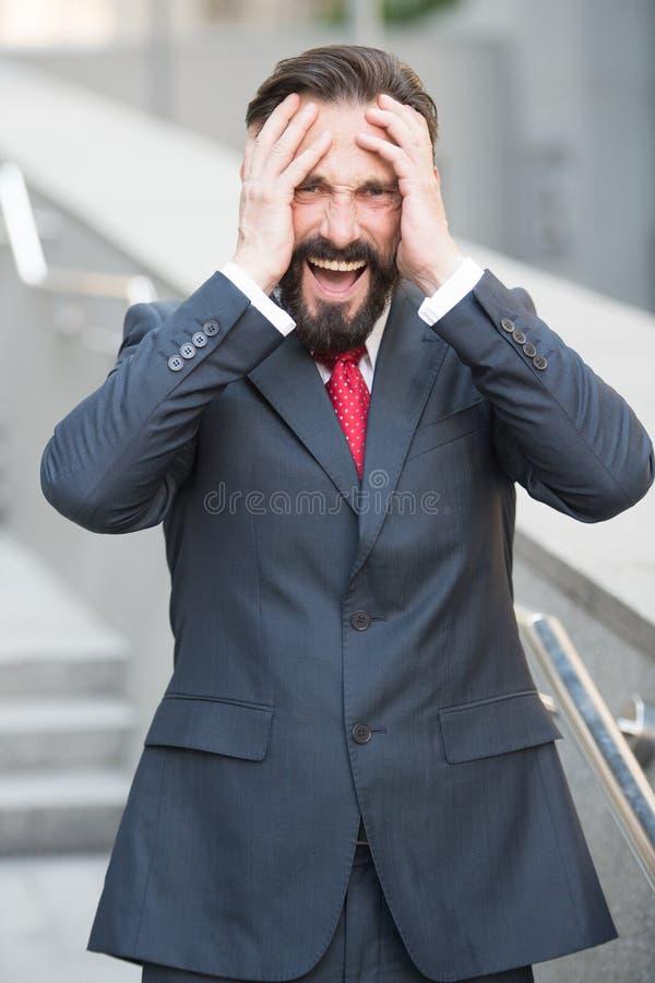 Homem de negócios desapontado que grita com mãos em sua cabeça fotografia de stock royalty free