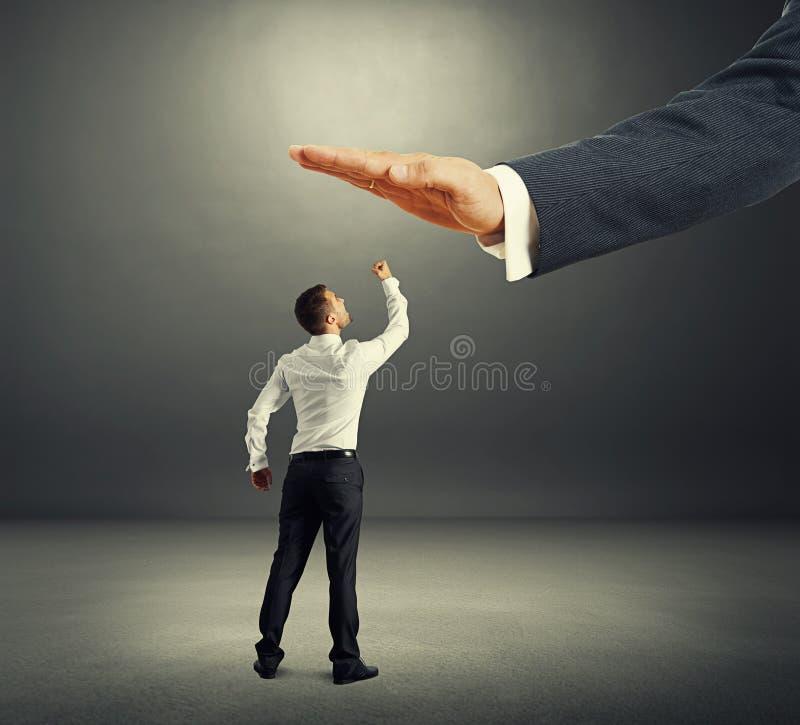 Homem de negócios descontentado que olha acima na palma grande imagem de stock royalty free