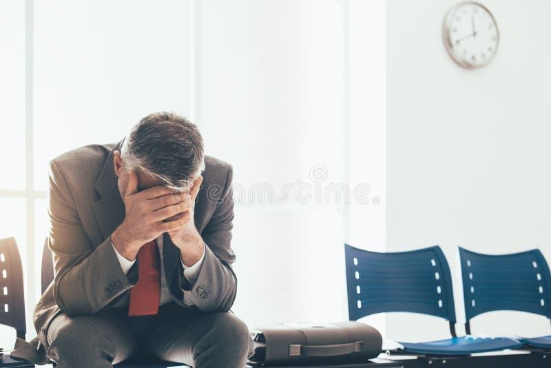 Homem de negócios desesperado na sala de espera imagens de stock royalty free