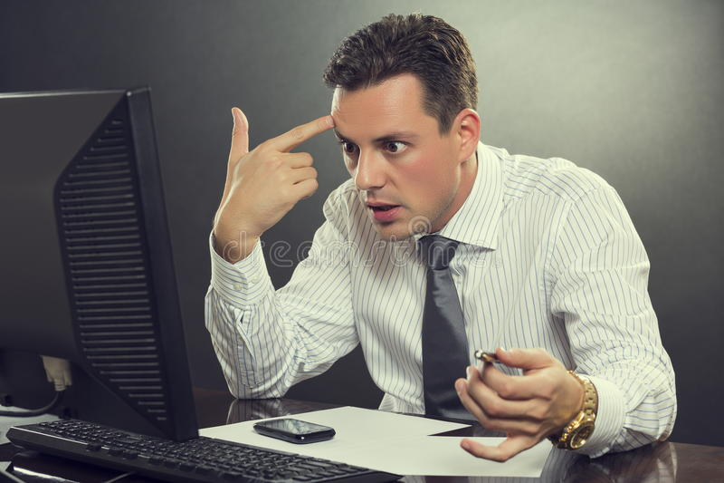Homem de negócios desesperado que aponta seu dedo a sua cabeça fotografia de stock royalty free