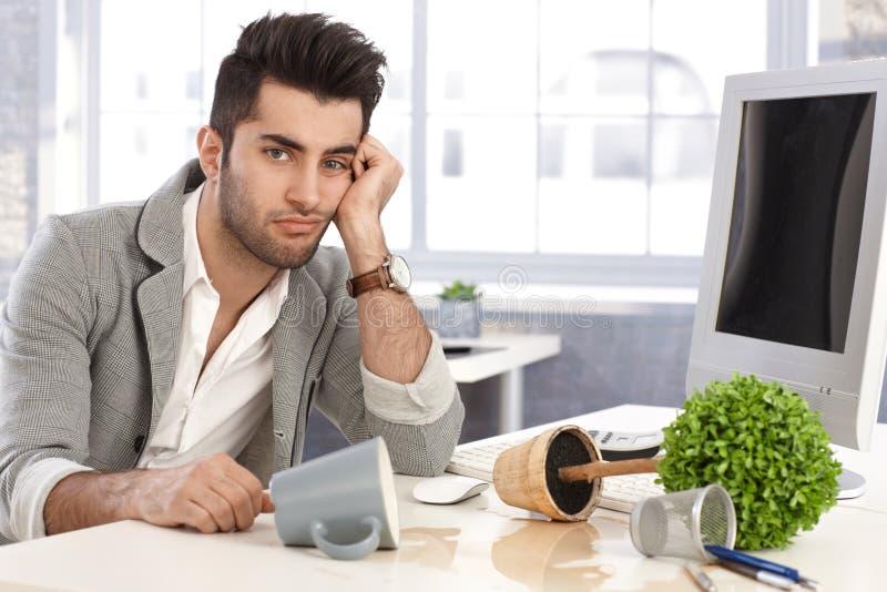 Homem de negócios desesperado que senta-se na mesa na desordem imagens de stock