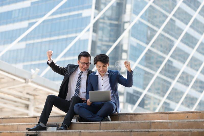 Homem de negócios do asiático dois feliz ao situar veja o portátil no busi foto de stock royalty free