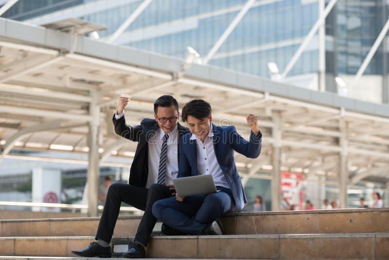 Homem de negócios do asiático dois feliz ao situar veja o portátil no busi imagens de stock