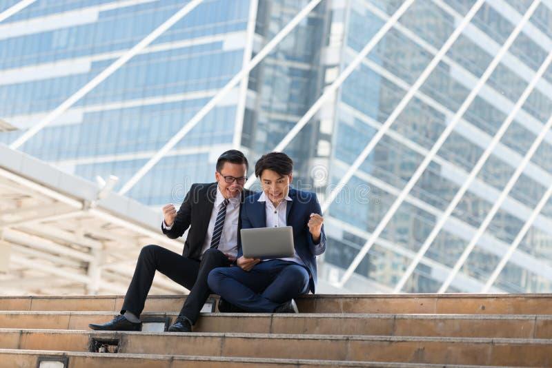 Homem de negócios do asiático dois feliz ao situar veja o portátil no busi fotografia de stock