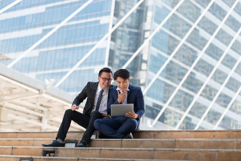 Homem de negócios do asiático dois feliz ao situar veja o portátil no busi imagens de stock royalty free
