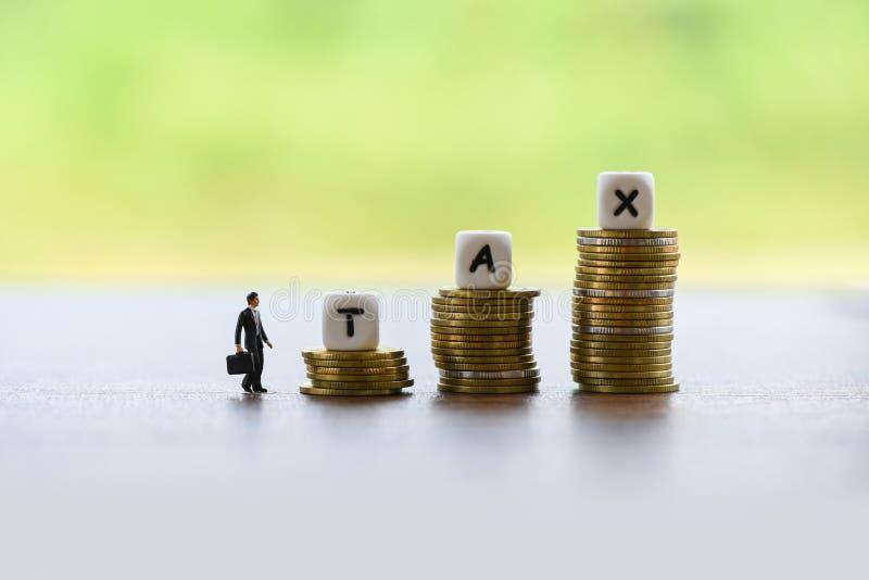 Homem de negócios do conceito e das finanças do aumento do imposto e moedas empilhadas imagens de stock royalty free