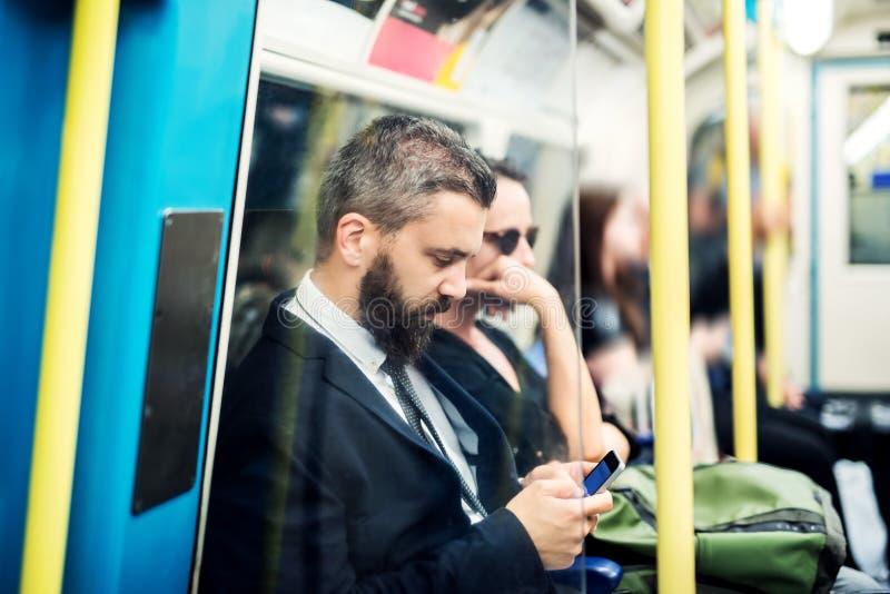 Homem de negócios do moderno com o smartphone dentro do metro na cidade, viajando ao trabalho fotos de stock royalty free