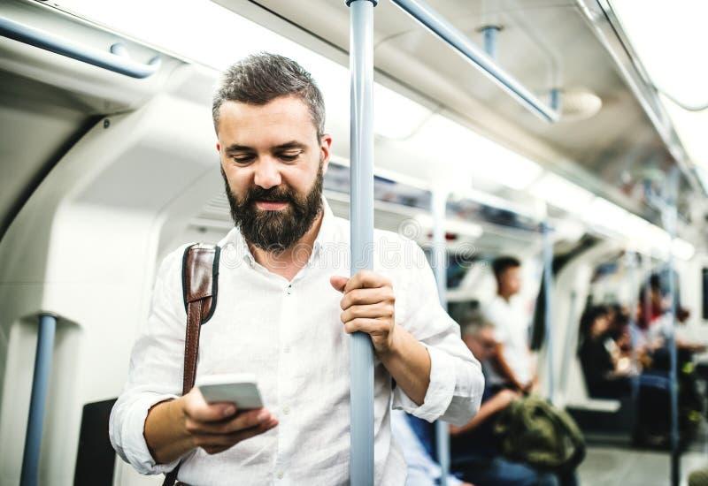 Homem de negócios do moderno com o smartphone dentro do metro na cidade, viajando ao trabalho fotografia de stock