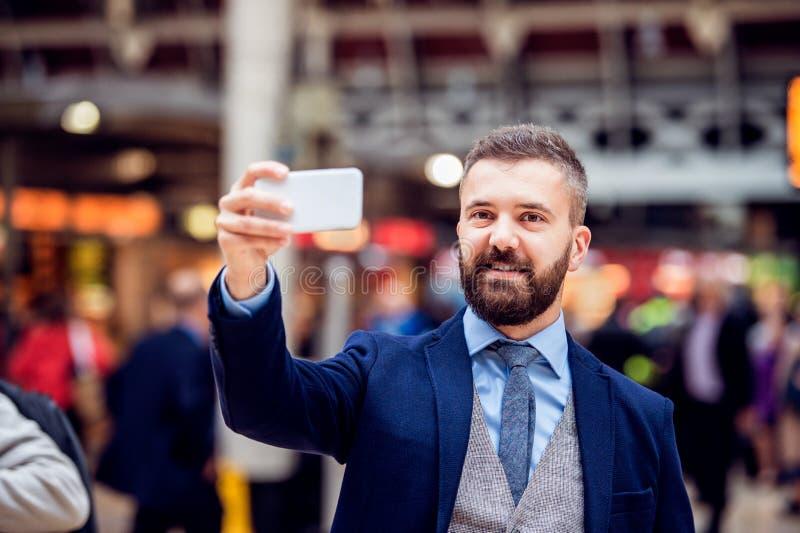 Homem de negócios do moderno com o smartphone que toma o selfie, trem aglomerado fotos de stock royalty free