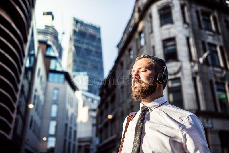 Homem de negócios do moderno com os fones de ouvido que estão na rua na cidade Copie o espaço imagens de stock