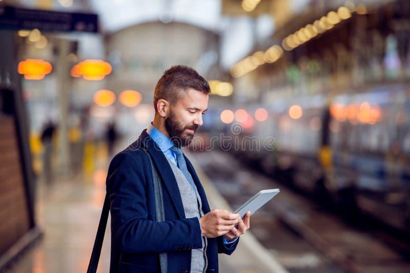 Homem de negócios do moderno com a tabuleta, esperando, plataforma do trem fotografia de stock royalty free