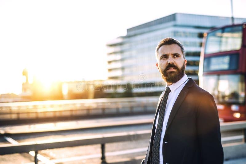 Homem de negócios do moderno que anda ao longo da estrada em Londres no por do sol Copie o espaço imagem de stock