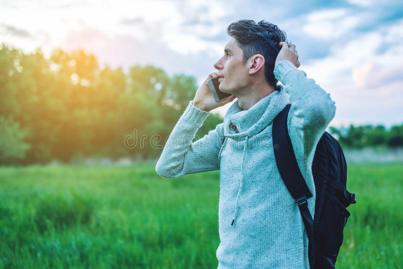 Homem de negócios do homem novo que fala no telefone celular fora em um campo de grama imagem de stock