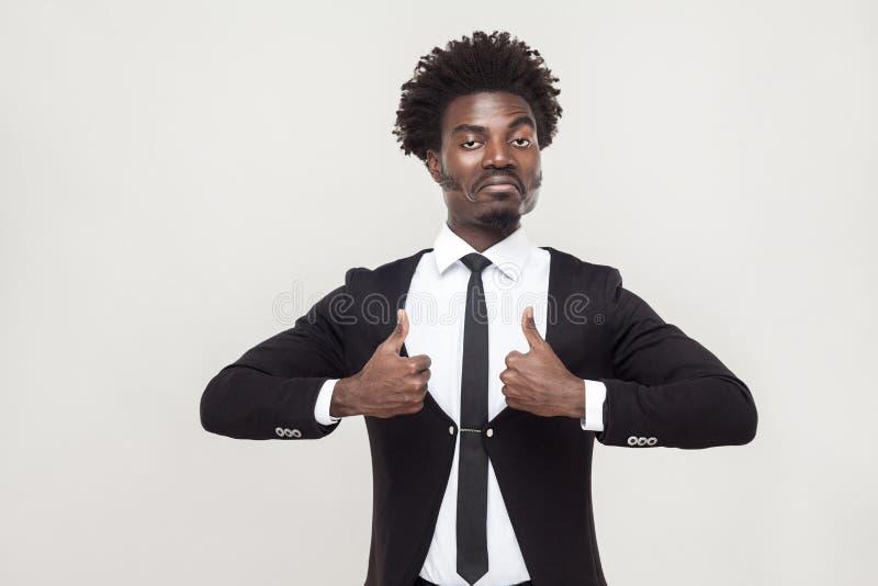 Homem de negócios do sucesso que olha a câmera e os polegares acima fotografia de stock