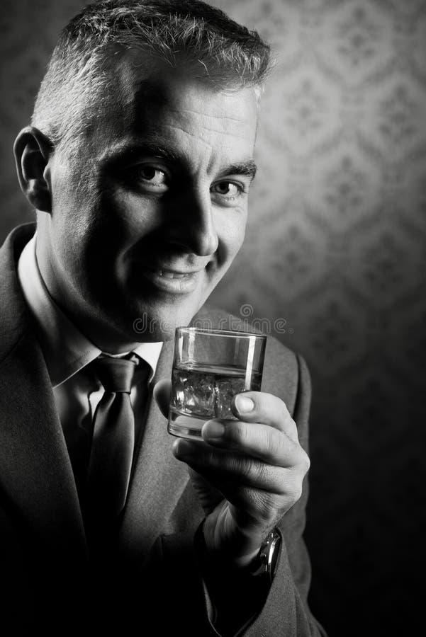Homem de negócios do vintage que guarda um vidro do uísque fotos de stock royalty free