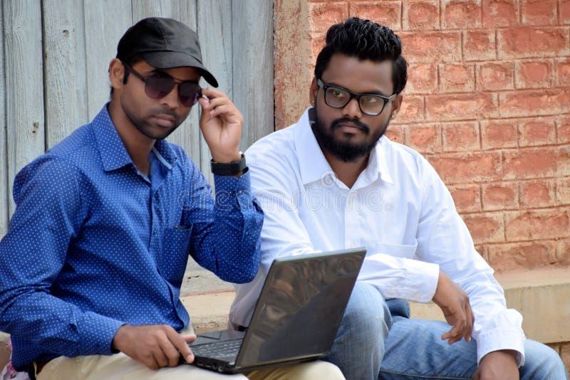 Homem de negócios dos jovens dois que usa o portátil em exterior imagens de stock