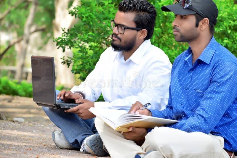 Homem de negócios dos jovens dois que usa o portátil & escrevendo o livro em exterior imagens de stock royalty free