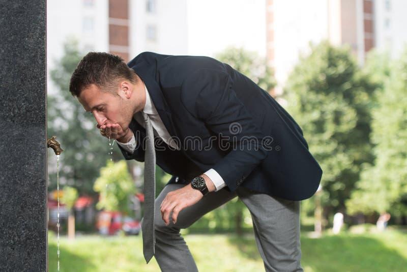 Homem de negócios Drinking Water foto de stock royalty free