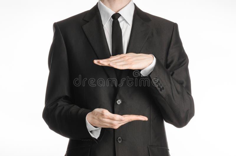 Homem de negócios e assunto do gesto: um homem em um terno e em um laço pretos que guardam duas mãos na frente dele e mostras o t fotografia de stock royalty free