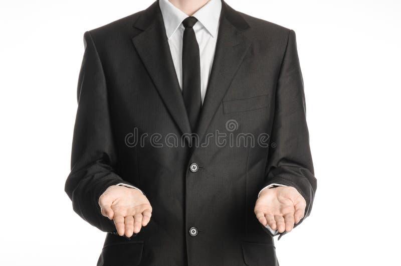 Homem de negócios e assunto do gesto: um homem em um terno e em um laço pretos que guardam duas mãos na parte dianteira isolada n fotos de stock