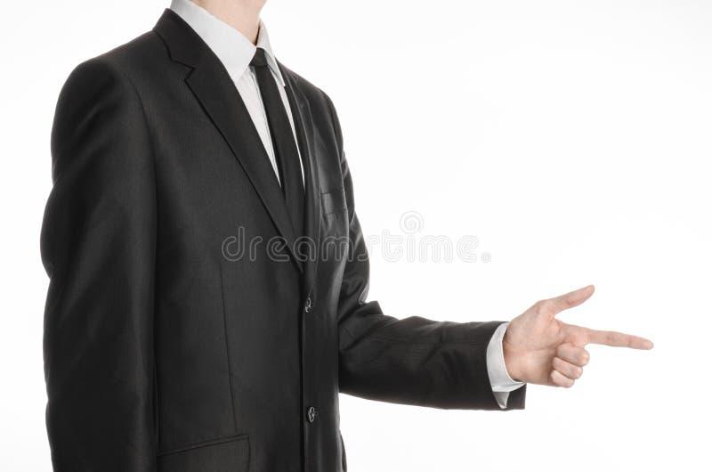 Homem de negócios e assunto do gesto: um homem em um terno e em um laço pretos que guardam sua mão na frente dele e das mostras q imagens de stock