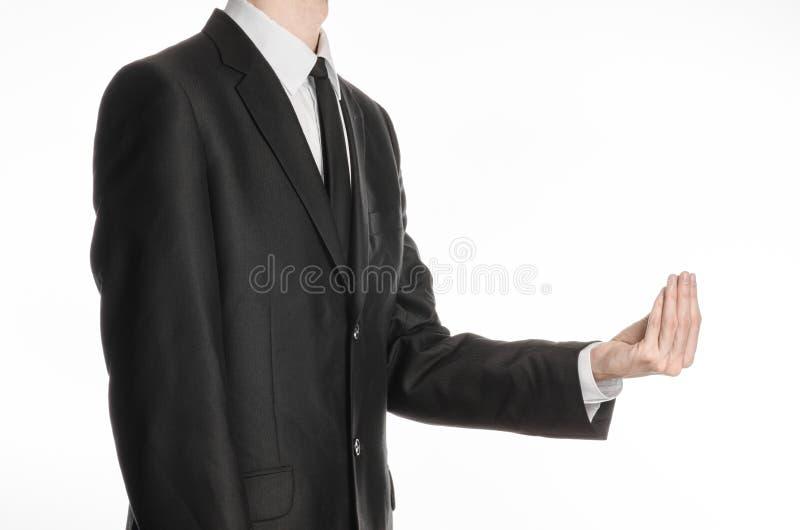 Homem de negócios e assunto do gesto: um homem em um terno e em um laço pretos que guardam sua mão na frente dele e mostras um ge imagens de stock