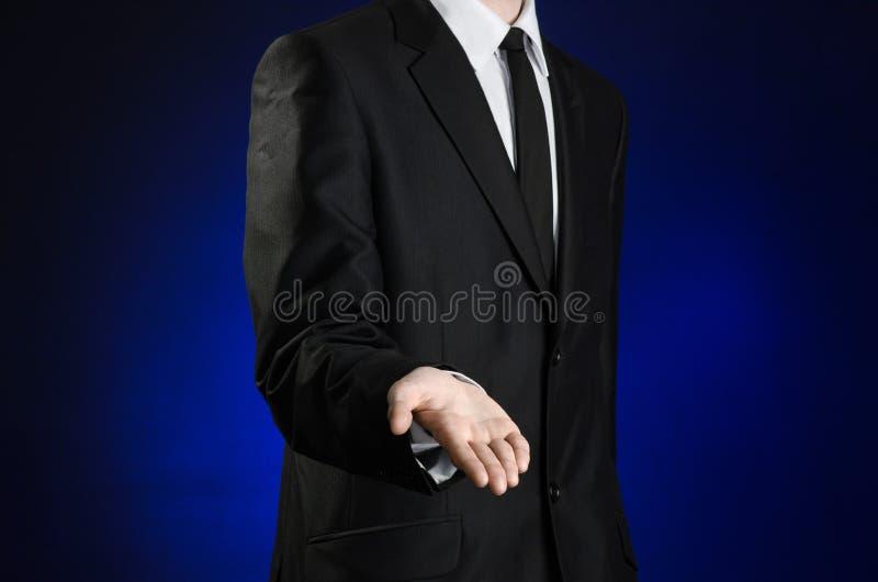 Homem de negócios e assunto do gesto: um homem em um terno preto e a camisa branca sustentam uma mão contra a obscuridade - fundo imagens de stock royalty free