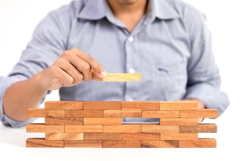 Homem de negócios e bloco de madeira proeminente do brinquedo fotografia de stock
