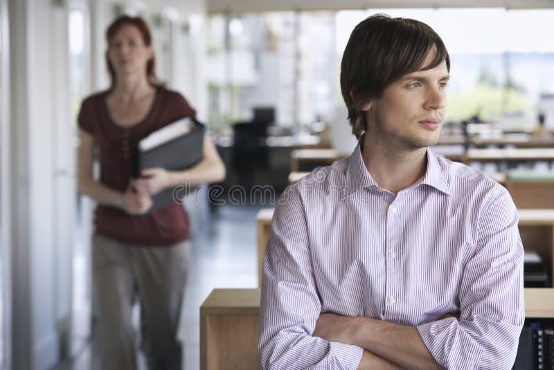 Homem de negócios e colega pensativos no escritório imagens de stock royalty free