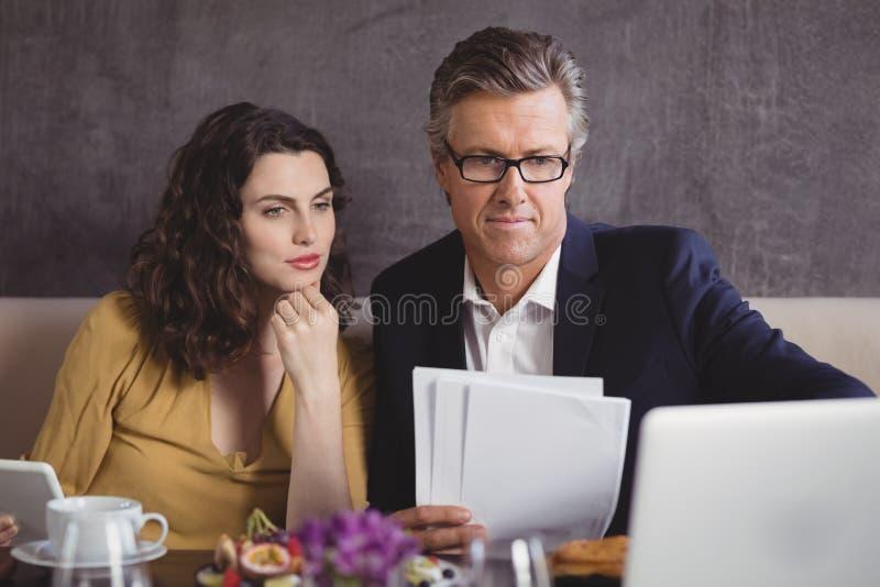 Homem de negócios e colega que trabalham sobre o portátil fotografia de stock