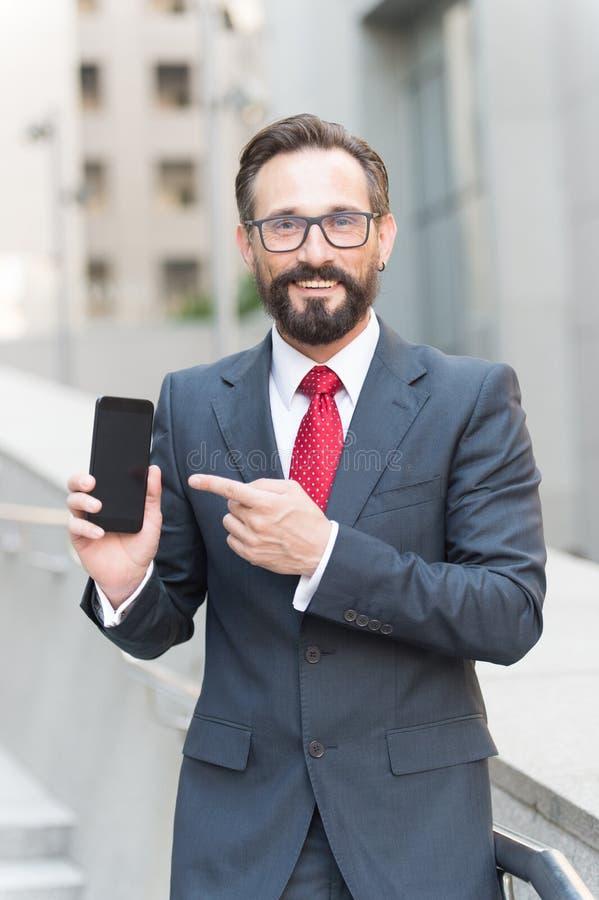 Homem de negócios e dispositivo digital Retrato do homem de negócios de sorriso que aponta o dedo no telefone celular da tela vaz fotos de stock