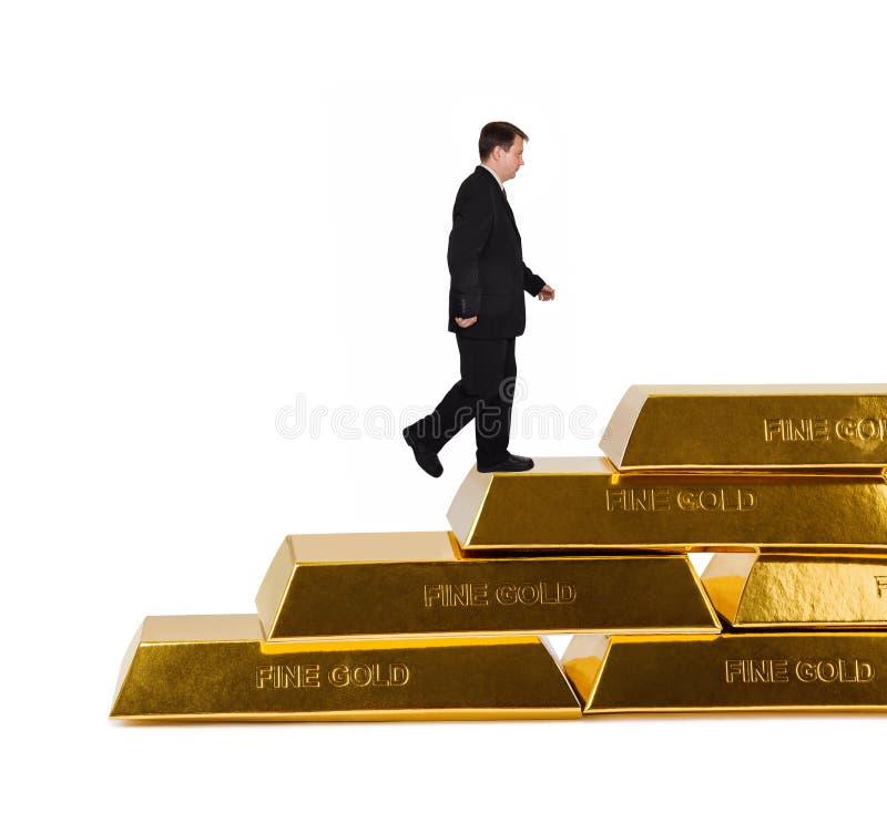 Homem de negócios e escadas feitos de barras de ouro fotografia de stock royalty free